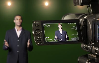 Television presenter in a green screen TV studio, seen through the LCD display of a digital camera. Selective focus on the viewfinder.